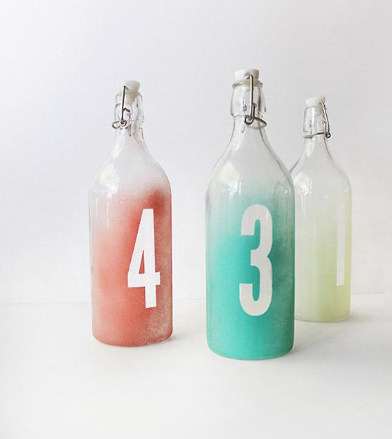Números de mesa en botellas de cristal